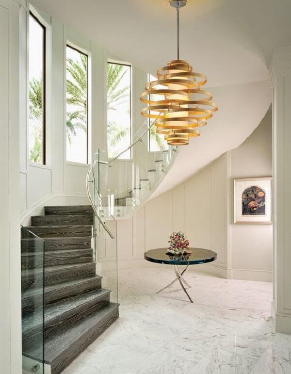 Lustre pendente para escada com design dourado. Fonte: Pinterest
