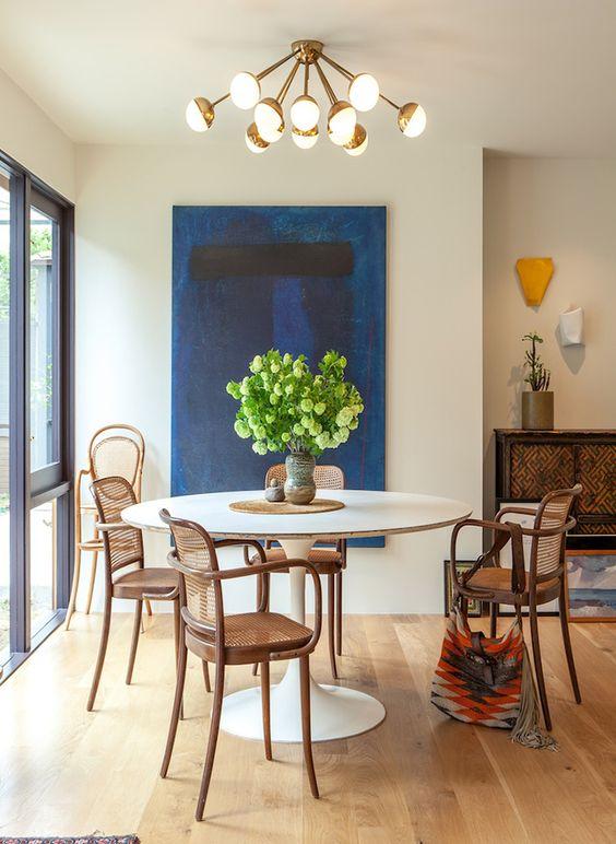 Mesa de jantar branca com cadeira de palha e madeira