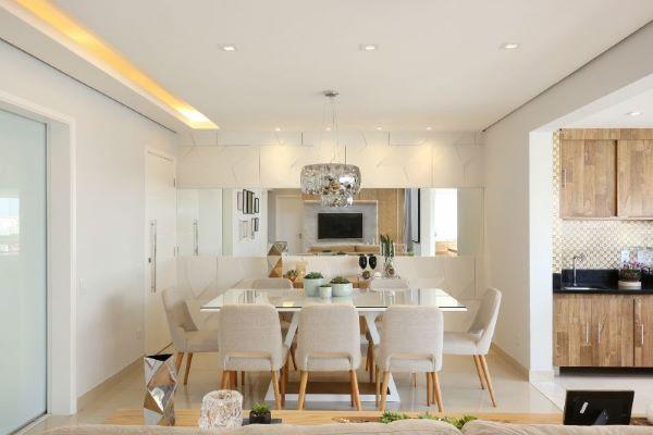 Mesa de jantar branca com tampo de vidro e cadeiras neutras