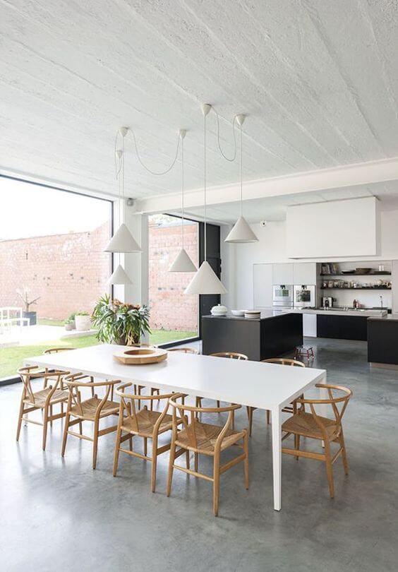 Mesa de jantar branca para varanda gourmet clean com piso de cimento queimado e cadeiras de madeira