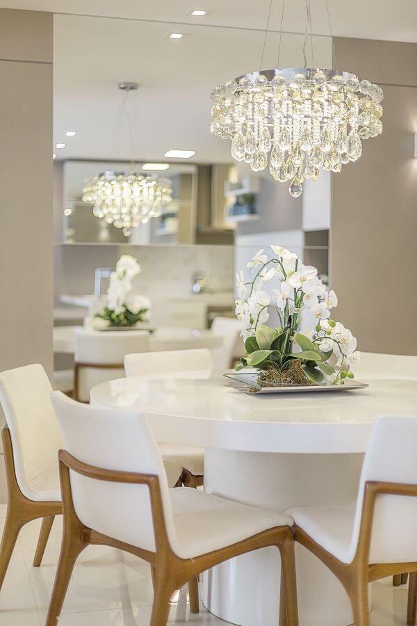 Mesa de jantar branca redonda com lustre de cristal e cadeiras brancas
