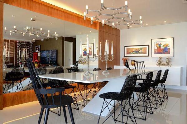Mesa de jantar branco com cadeiras pretas lustre moderno e parede de espelho