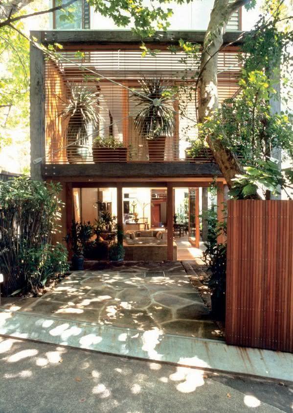 Modelos de garagem com portão de madeira e plantas na decoração
