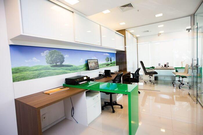 O gaveteiro escritório branco fica camuflado embaixo da mesa verde. Projeto de DH Arquitetura