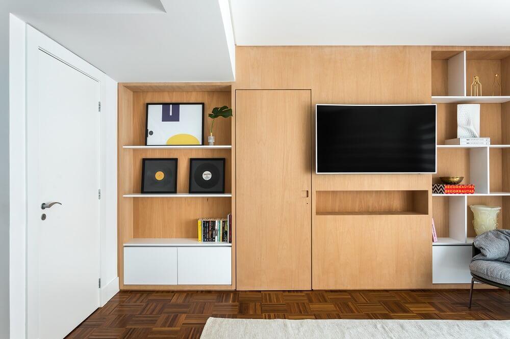 O painel com nichos da TV foi desenhado incorporando a porta do closet ao conjunto. Foto: Eduardo Macarios