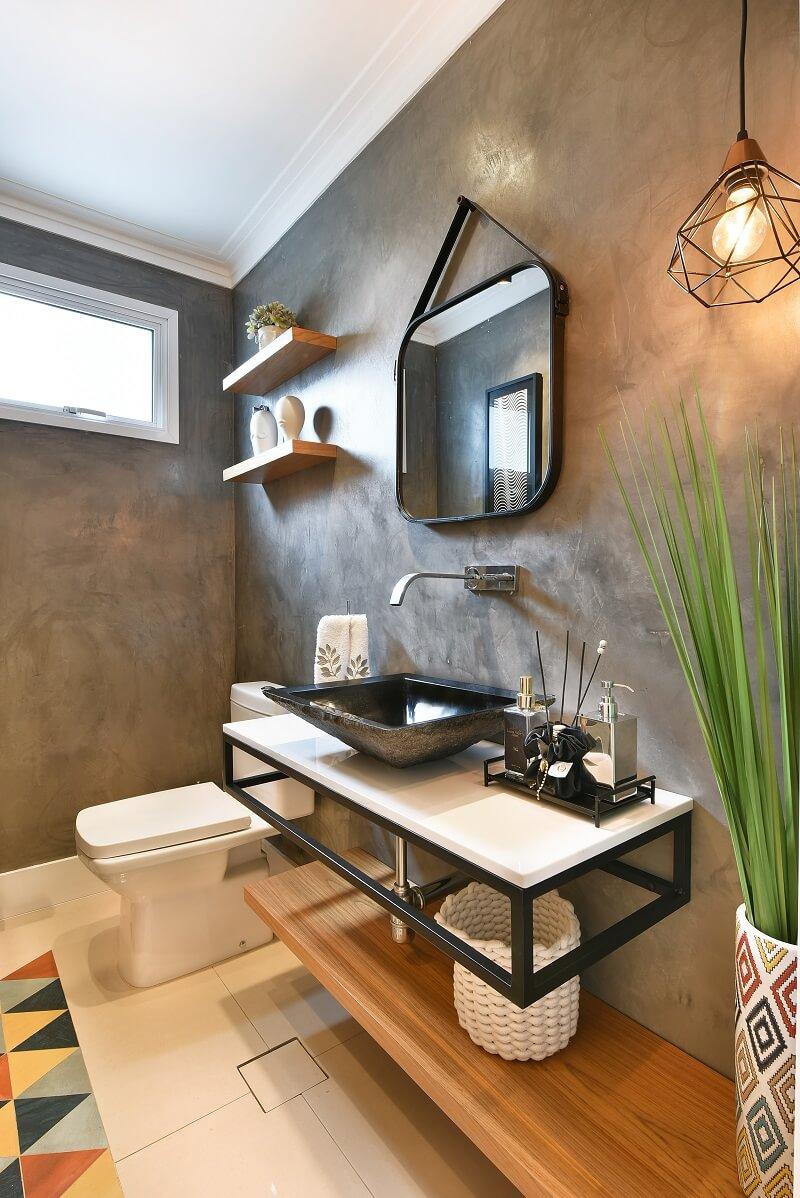 Parede de cimento queimado, pendente aramado e elementos em madeira decoram o lavabo do imóvel. Foto: Sidney Doll
