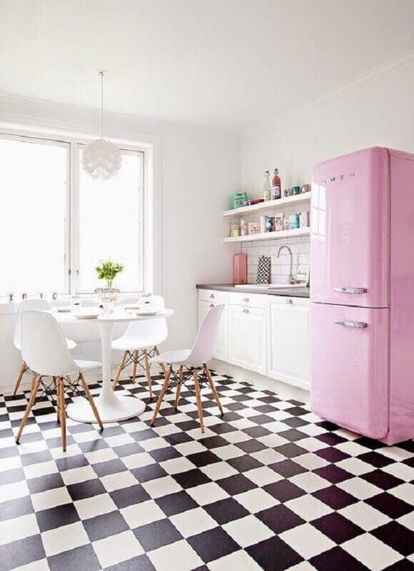 Piso preto e branco xadrez para cozinha branca decorada com geladeira rosa e mesa redonda Foto Roomed