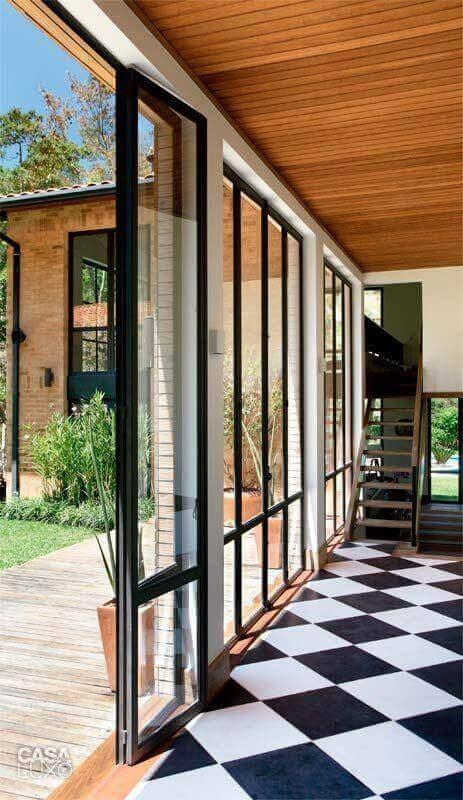 Piso preto e branco xadrez para decoração de casa com portas de vidro Foto MCA Estúdio