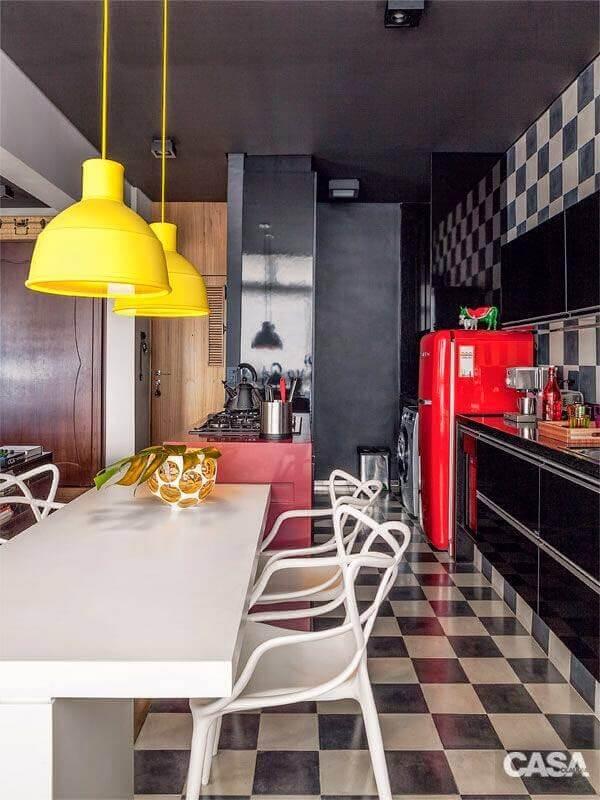 Piso xadrez para cozinha preta decorada com luminária amarela e geladeira vermelha Foto Casa Abril