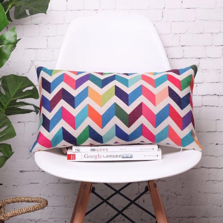Poltrona branca com almofadas grandes e coloridas