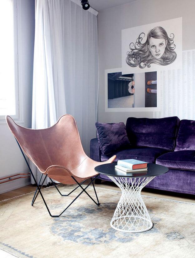 Poltrona butterfly caramelo na sala com sofá roxo e tapete moderno