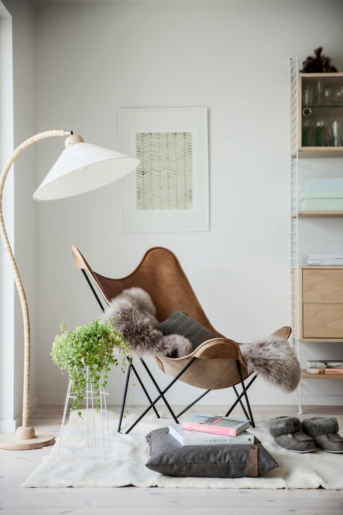 Poltrona butterfly com manta cinza de pelo e decoração moderna