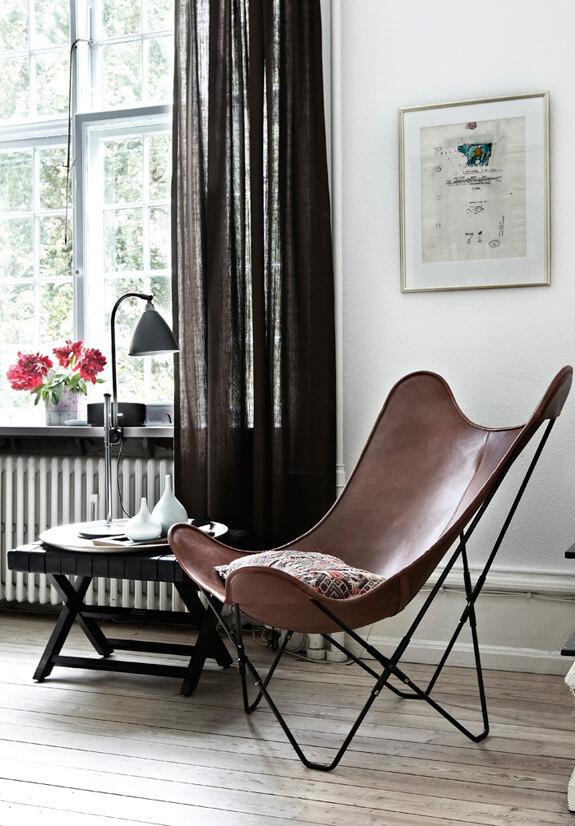 Poltrona butterfly couro marrom na sala de estar de madeira
