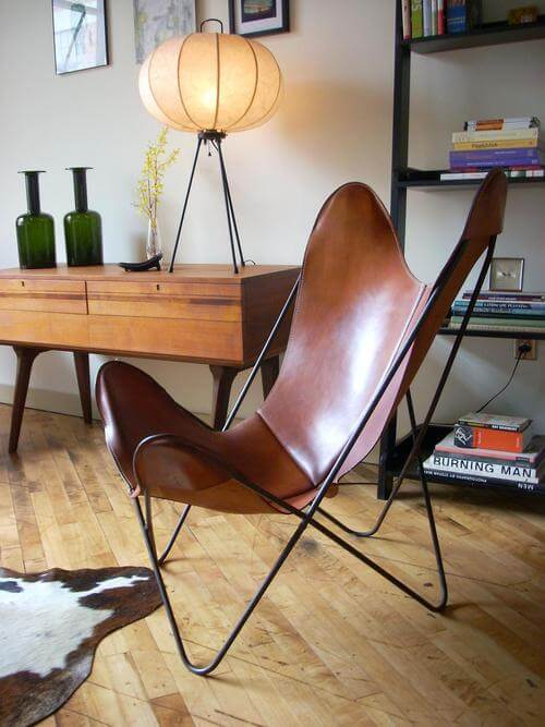 Poltrona butterfly de couro caramelo na sala criativa estilo retro