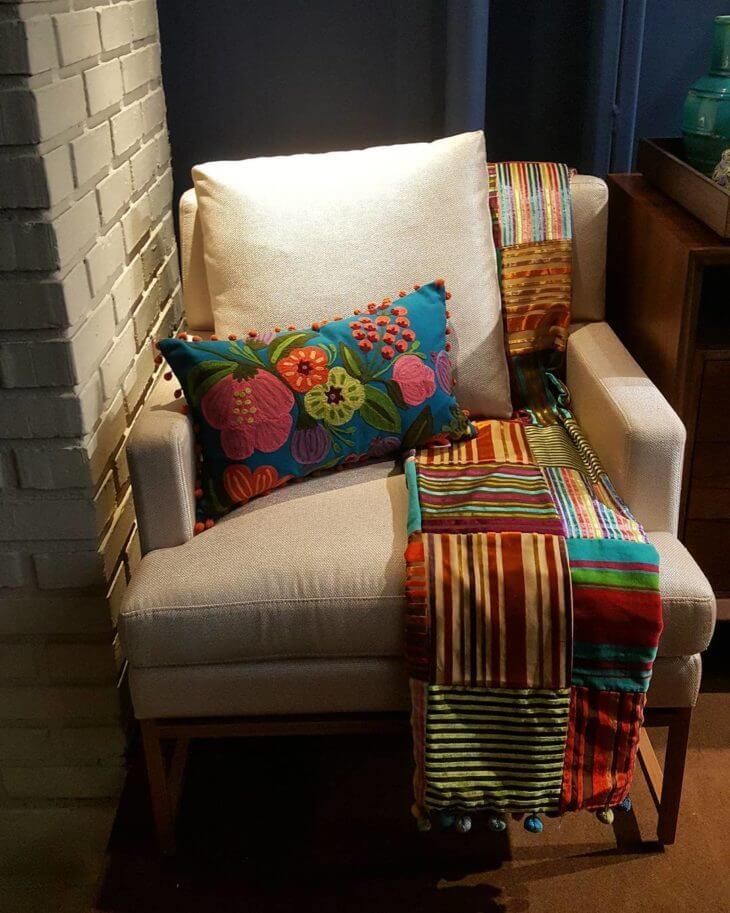 Poltrona com almofadas grandes e manta colorida