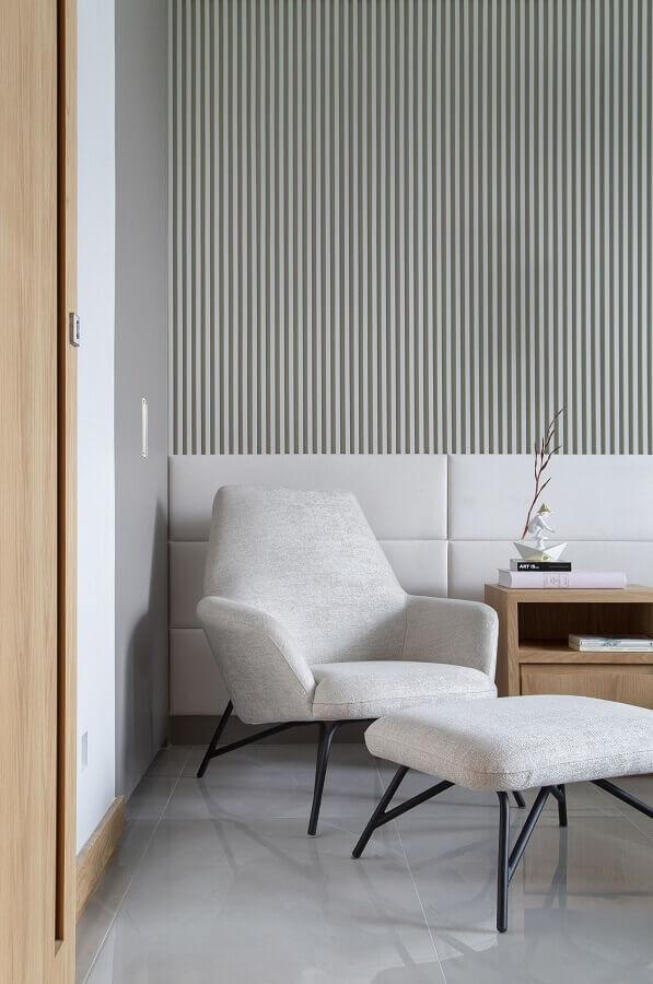 Poltrona confortável para quarto decorado com papel de parede listrado e cabeceira branca estofada Foto Casa de Valentina
