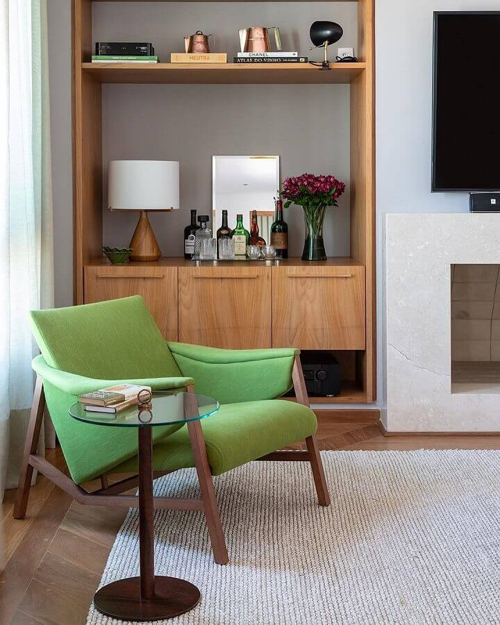 Poltrona confortável para sala de TV decorada com estante de madeira Foto Adriana Valle e Patrícia Carvalho