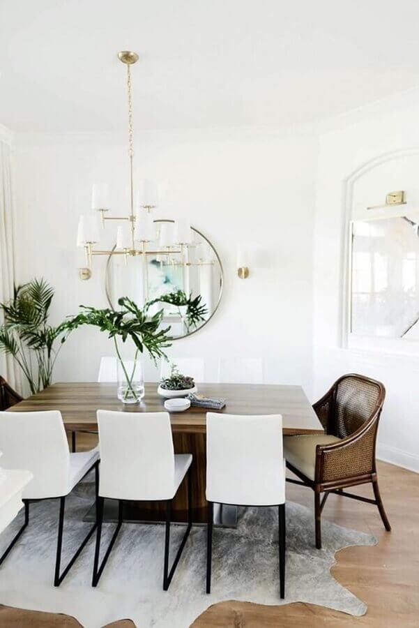 Poltrona confortável para sala de jantar branca decorada com espelho redondo Foto The Ever Girl