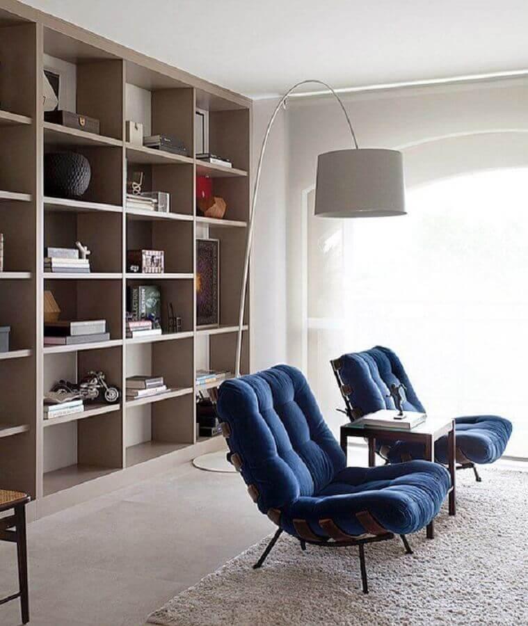 Poltrona confortável para sala decorada com estante de nichos e luminária de piso Foto Pinterest