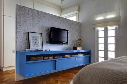 Quarto com rack azul e papel de parede no painel