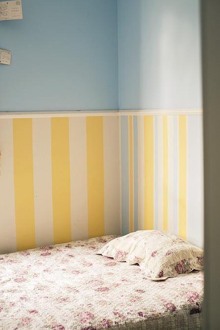 Quarto com rodameio e papel de parede listrado em azul e amarelo