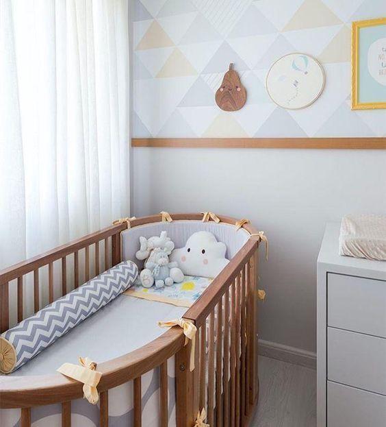 Quarto de bebe com rodameio de madeira e papel de parede triangular