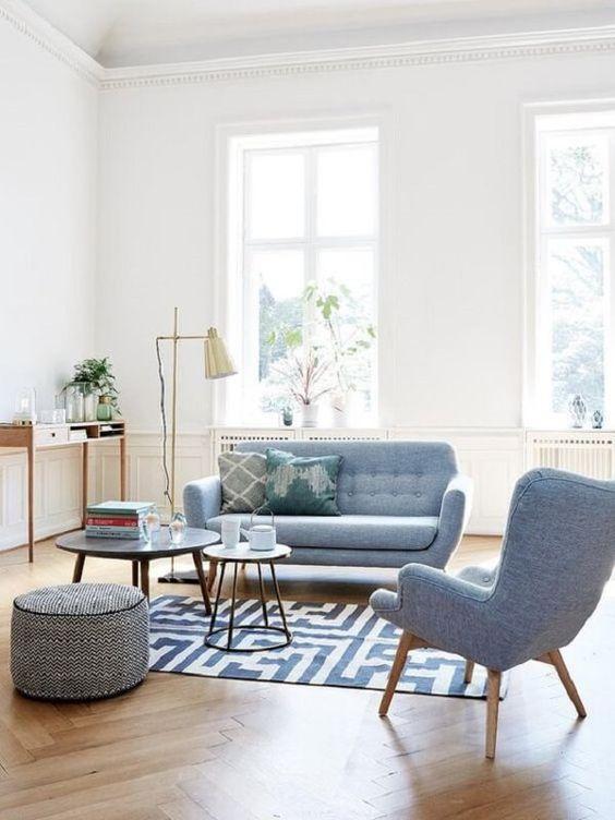 Sala azul com sofá pé palito e poltrona