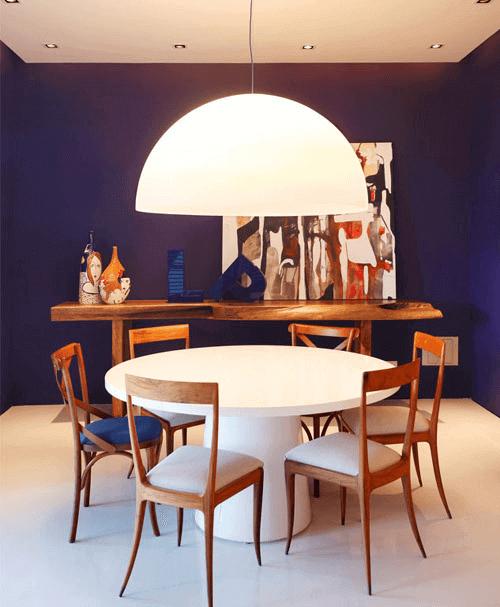 Sala azul moderna com mesa de jantar redonda branca e cadeiras de madeira