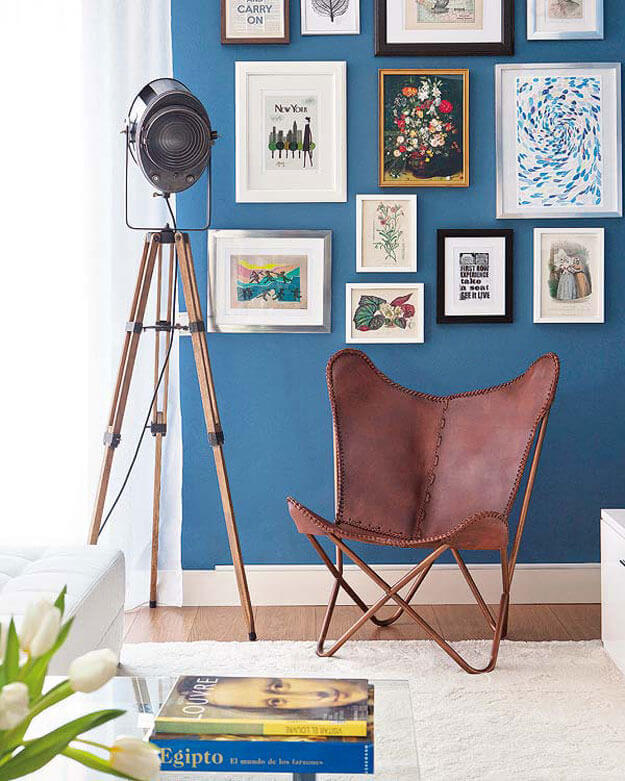 Sala azul moderna com poltrona butterfly couro marrom e moveis de madeira criativos