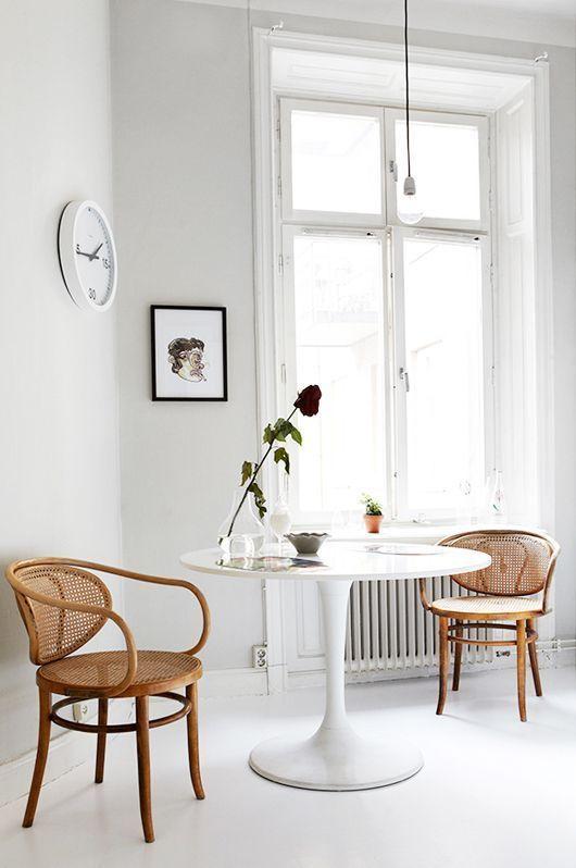 Sala com cadeira de palha e mesa de jantar branca