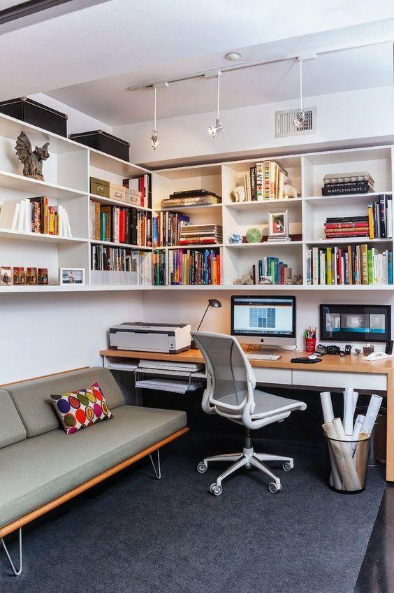 Sala com home office e estante na parede
