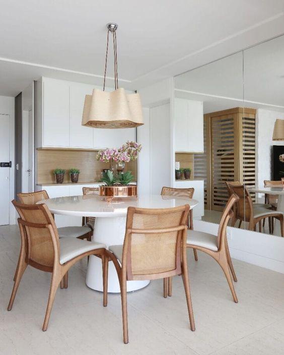 Sala com mesa de jantar branca e cadeiras de madeira