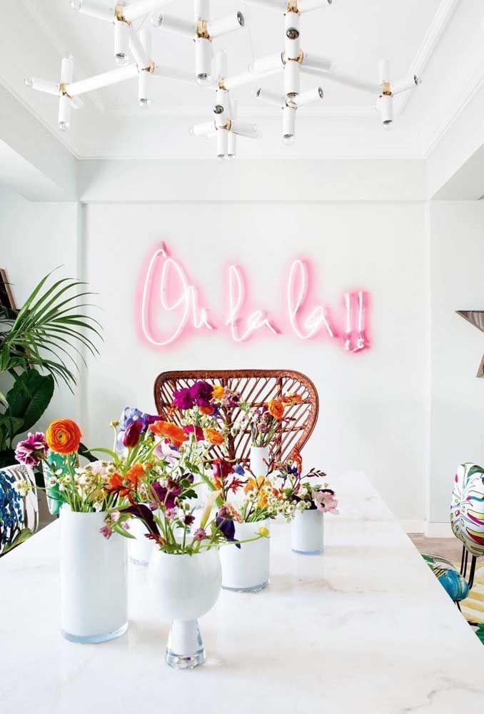 Sala com mesa de jantar branca e letreiro de luz neon