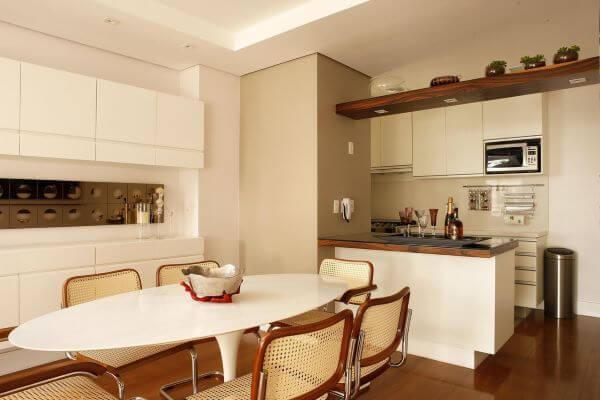 Sala com mesa de jantar branca oval e cadeiras de palha