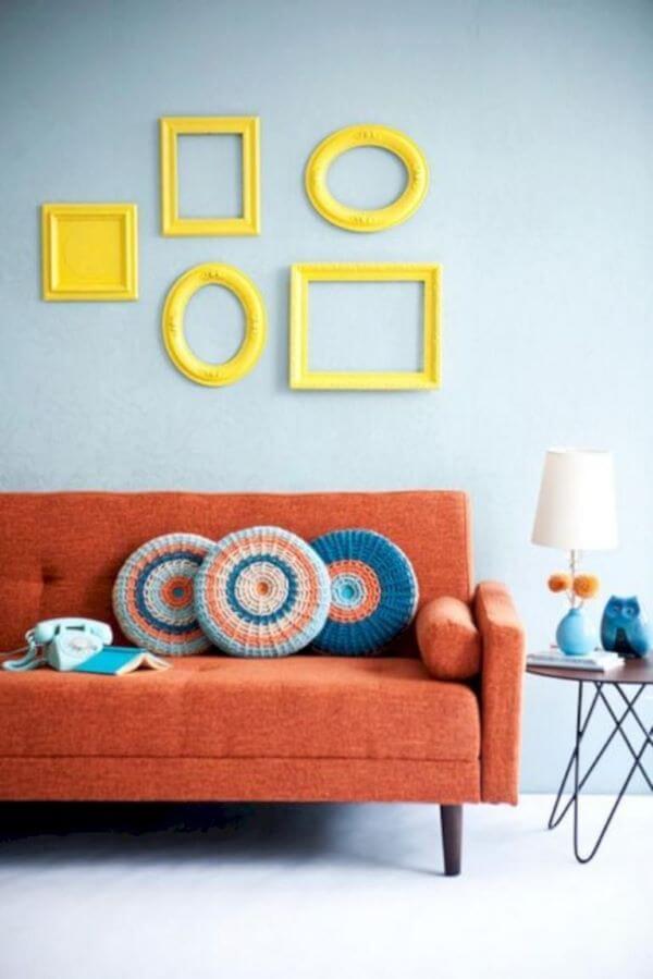 Sala com moldura colorida amarela e sofa pé palito na cor salmão