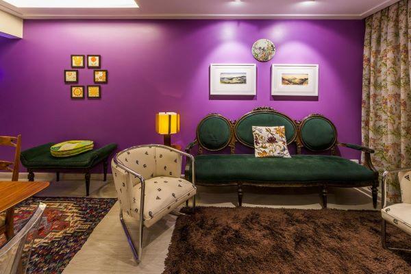 Sala com parede roxa e móveis vintage verde e madeira