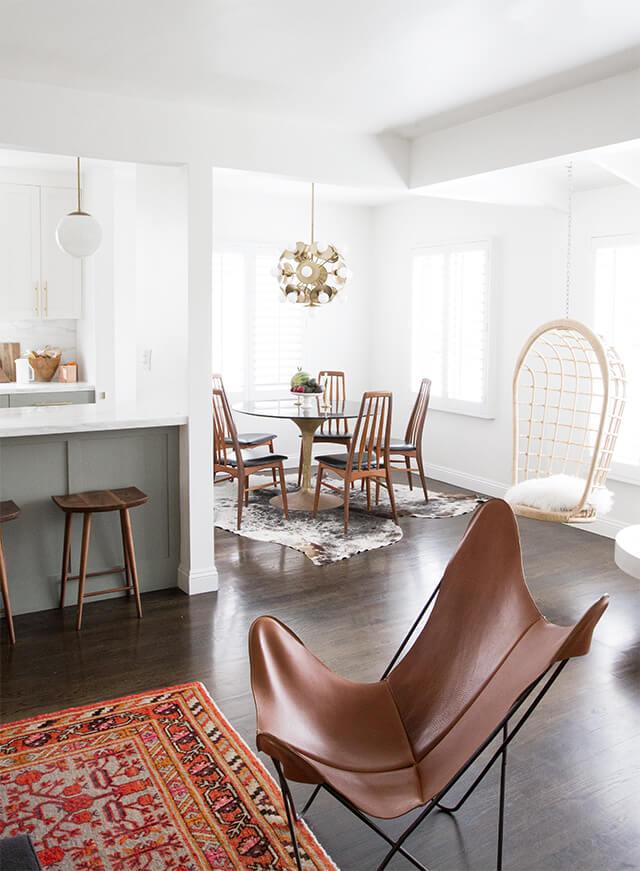 Sala com poltrona butterfly de couro marrom e tapete estampado colorido