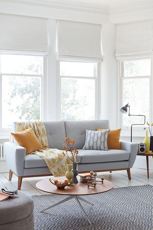 Sala com sofá pé palito cinza e almofadas coloridas