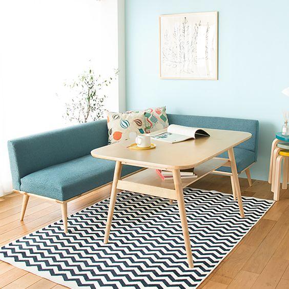 Sala com sofá pé palito e mesa de jantar de madeira retrô