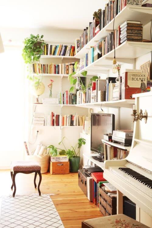 Sala de TV com estante de canto, tv e piano branco