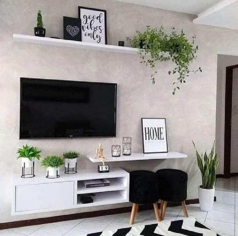 Sala de TV decorada com puff banqueta preto e parede de cimento queimado Foto Fashion Bubbles