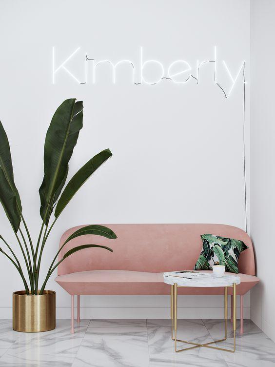 Sala de espera pequena com sofá pé palito rosa e vaso de plantas grandes