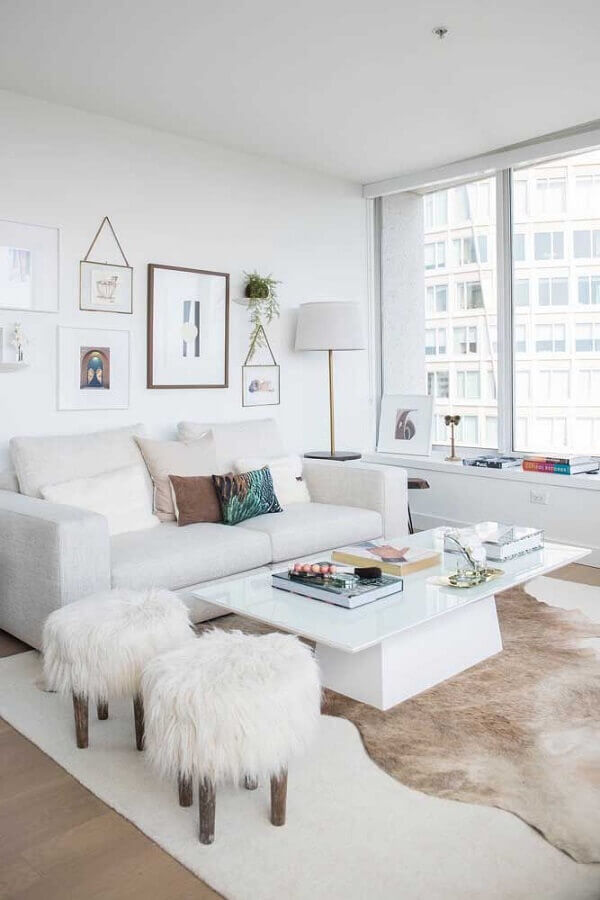 Sala de estar branca decorada com tapete de couro e puff banqueta redondo Foto Apartment Therapy