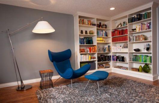 Sala de estar com estante de canto e poltrona azul