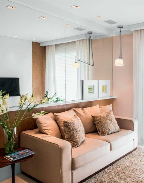 Sala de estar com rodameio e parede de espelho e madeira
