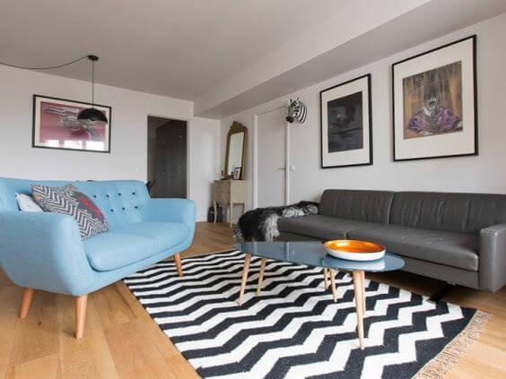 Sala de estar com tapete chevron preto e branco e sofá pé palito