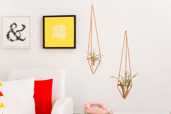 Sala de estar com vaso de ferro suspenso dourado e plantas aéreas