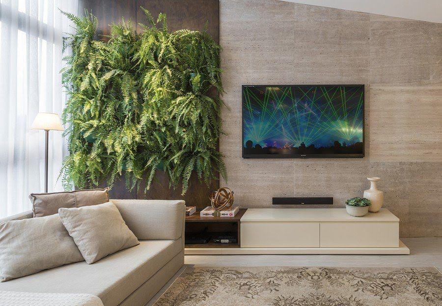 Sala de estar decorada com parede de samambaias e parede revestida com porcelanato