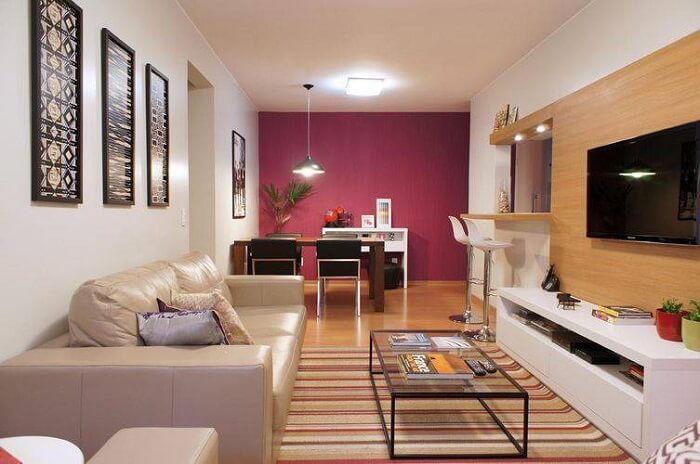 Sala de estar planejada pequena onde o acabamento do rack se conecta com a bancada da cozinha. Projeto de Giselle Medeiros