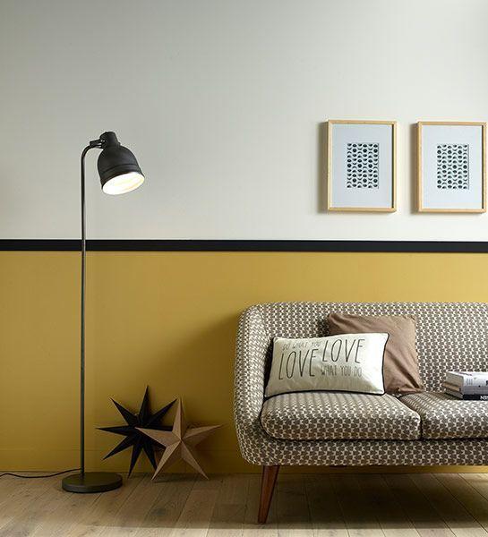 Sala de estar retrô com rodameio preto e parede mostarda